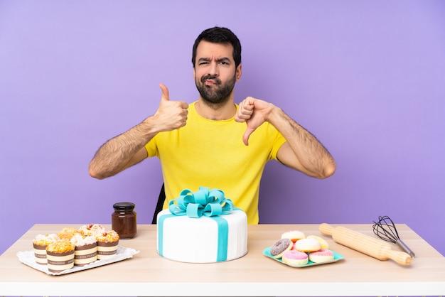 Uomo in una tabella con una grande torta che fa segno buono-cattivo. indeciso tra sì o no