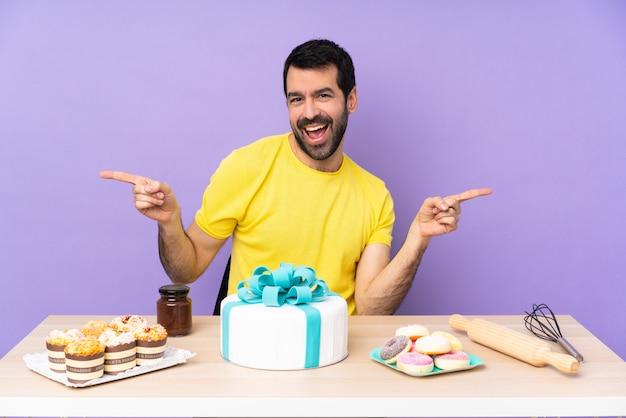 Uomo in un tavolo con una grande torta che punta il dito ai lati e felice