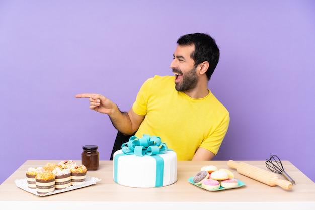 Uomo in un tavolo con una grande torta che punta il dito verso il lato