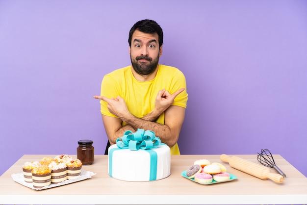Uomo in un tavolo con una grande torta che punta alle laterali che hanno dubbi