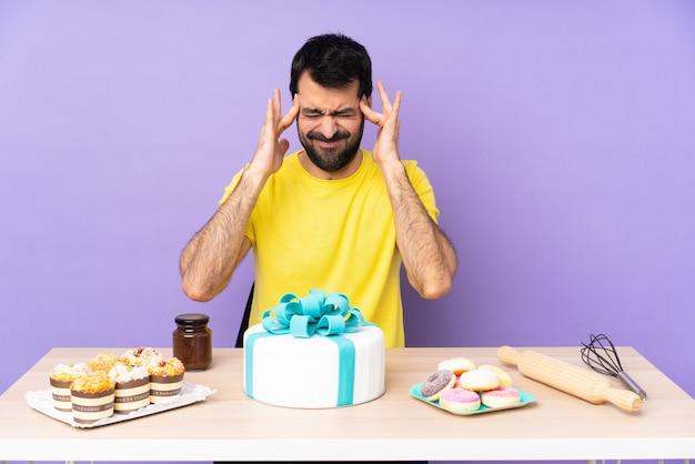 Uomo in un tavolo con una grande torta con mal di testa