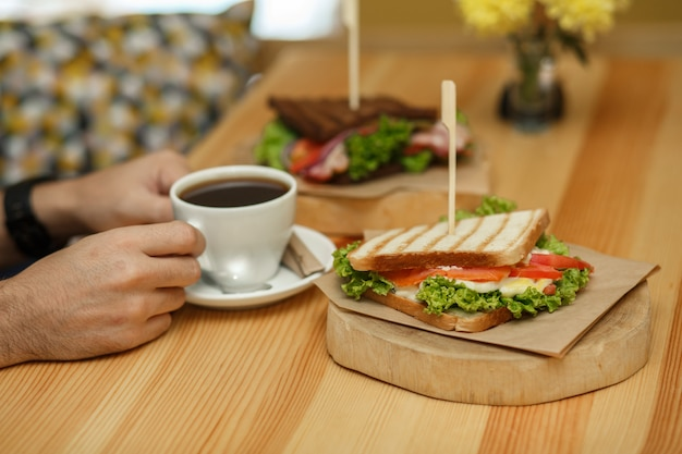 L'uomo prende una tazza di caffè da un tavolo di legno