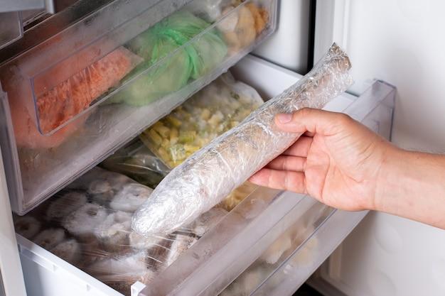 L'uomo tira fuori il pesce congelato dal congelatore. pesce surgelato. surgelato