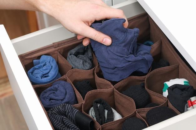 Un uomo prende calzini e mutandine piegati secondo il metodo di marie kondo. stoccaggio verticale dei vestiti in una cassettiera. organizzazione dello stoccaggio. ordine e pulizia. precisione.