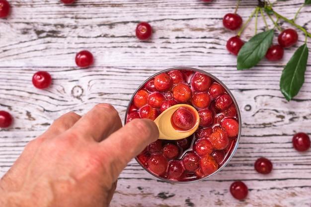Un uomo prende una bacca di ciliegia di un cucchiaio di legno da una ciotola di marmellata