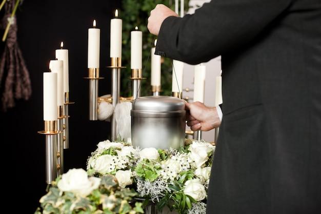 Uomo che cattura urna funebre con candele e fiori