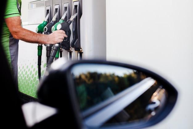 Uomo che prende una pompa di benzina per riempire