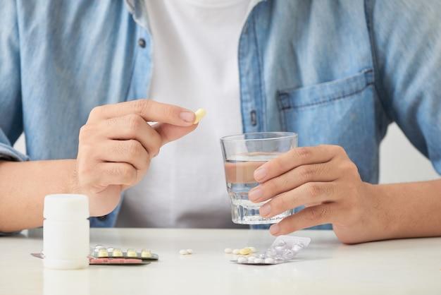 Uomo che prende le pillole sul divano in soggiorno