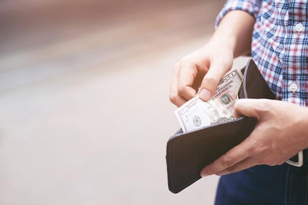 Uomo che prende soldi dal suo portafoglio.