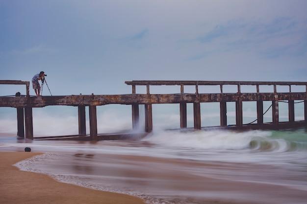 Uomo che cattura una fotografia del molo sulla spiaggia in un giorno di tempesta di pioggia