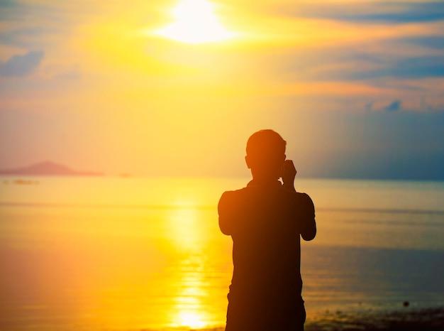 Uomo che prende le foto del tramonto