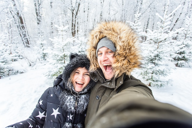 Uomo che prende selfie foto giovane coppia romantica sorriso neve foresta inverno all'aperto.