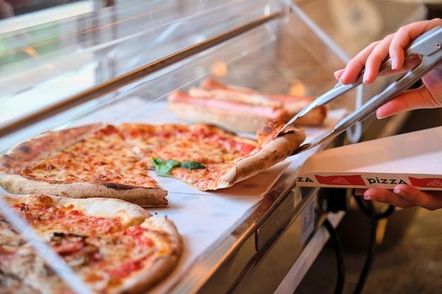 Uomo che prende una fetta di pizza da una vetrina