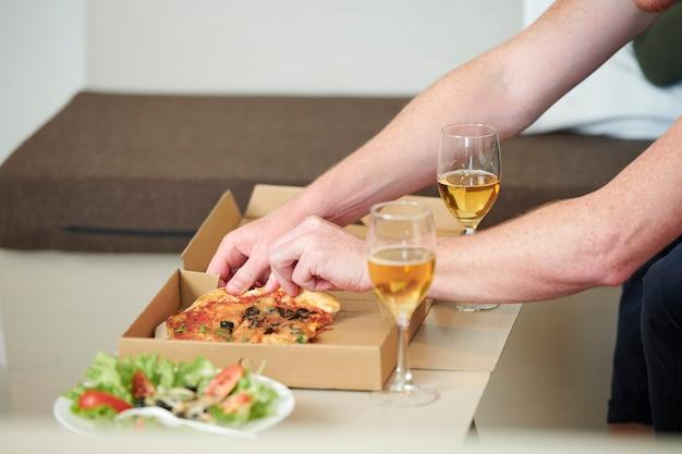 Uomo che prende la fetta di pizza