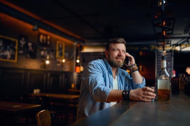Uomo che parla al cellulare al bancone del bar