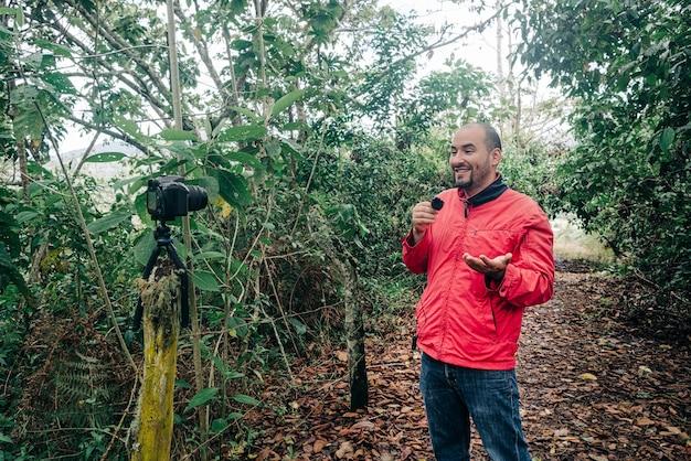 Uomo che parla in un microfono durante la registrazione in un luogo immerso nella natura