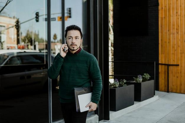 Uomo che parla al telefono portando un tablet digitale e un notebook