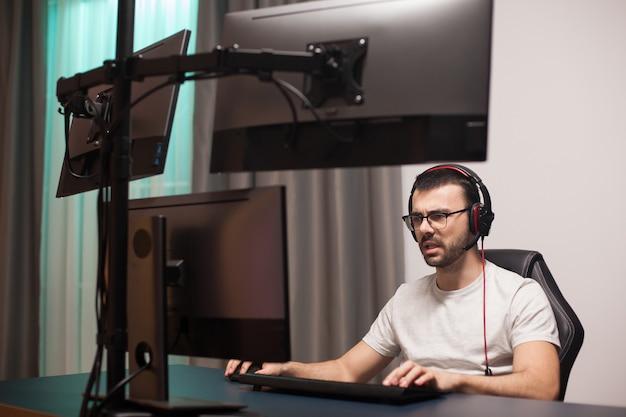 Uomo che parla con altri giocatori che usano le cuffie con microfono mentre giocano a sparatutto in streaming.