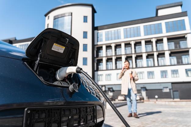 L'uomo parla al telefono mentre la sua auto è in carica alla stazione