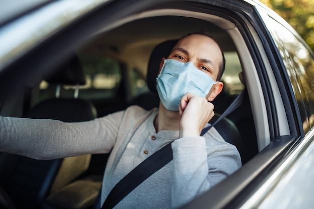 Un tassista uomo guida un'auto e regola la mascherina medica durante l'epidemia di coronavirus.
