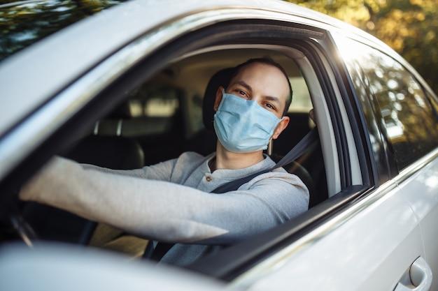 Un tassista uomo guida un'auto con indosso una mascherina medica durante l'epidemia di coronavirus.