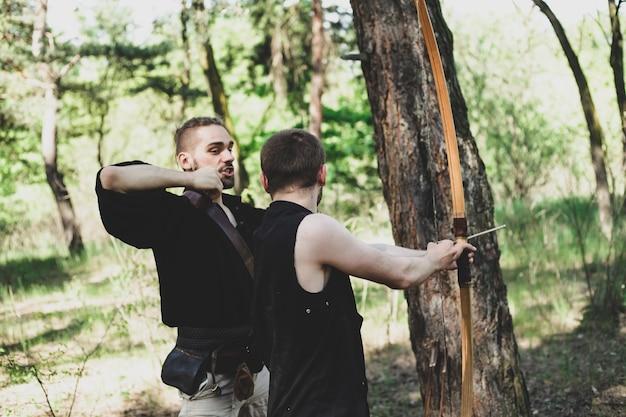 Un uomo insegna a tirare con l'arco il ragazzo tiene un arco in mano