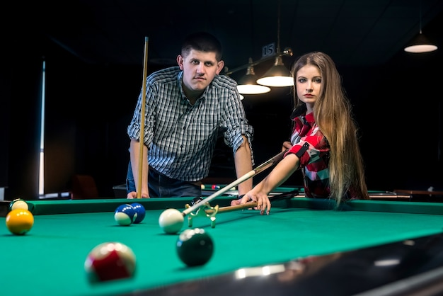 Uomo che insegna alla sua ragazza a giocare a biliardo, coppia in un pub