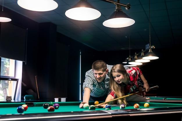 Uomo che insegna alla sua ragazza che gioca a biliardo, coppia in pub