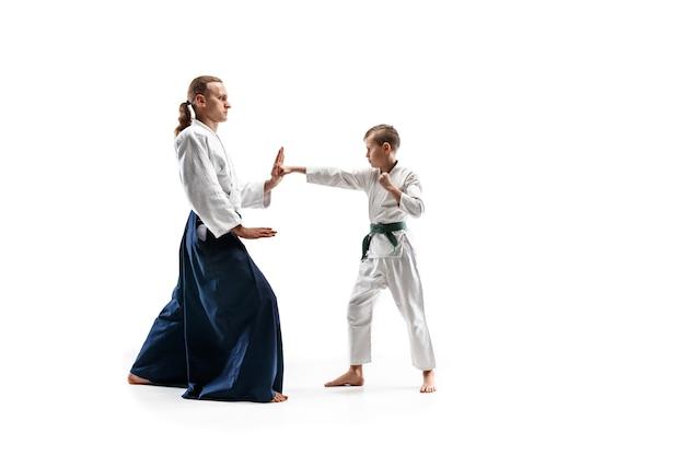 Uomo e ragazzo adolescente che combattono all'addestramento di aikido nella scuola di arti marziali. stile di vita sano e concetto di sport. combattenti in kimono bianco sul muro bianco. uomini di karate con facce concentrate in uniforme.
