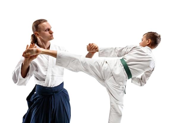 Uomo e ragazzo adolescente che combattono durante l'allenamento di aikido nella scuola di arti marziali