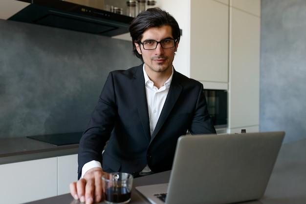 L'uomo telelavoro lavora a casa con un laptop