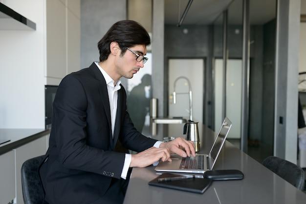 L'uomo telelavoratore lavora a casa con un laptop