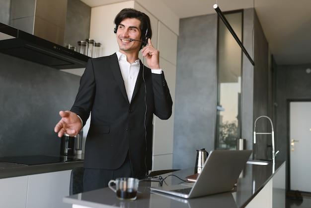 L'uomo telelavoro lavora a casa con uno smartphone