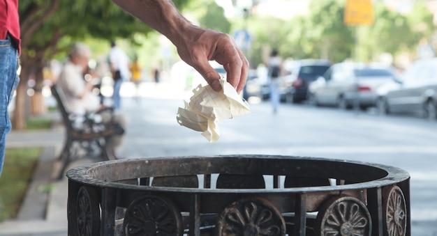 Uomo che getta immondizia in un bidone della spazzatura.