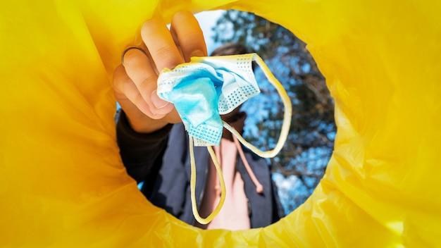 Uomo che getta una maschera medica in un bidone della spazzatura.