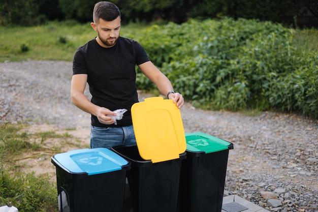 Uomo che getta un sacchetto di plastica nel cestino per il riciclaggio nel cortile sul retro di diversi colori sui bidoni di plastica verde
