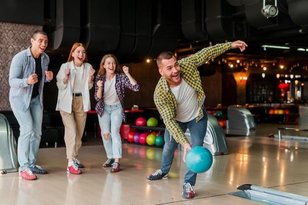 Uomo che lancia una palla da bowling turchese
