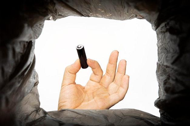 Un uomo getta una batteria viene utilizzata in un bidone della spazzatura. vista dal basso dal cestino. problema del riciclaggio e dell'inquinamento del pianeta con i rifiuti.