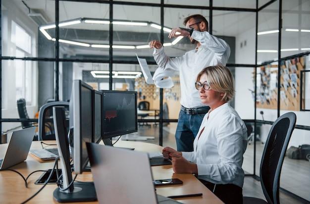 L'uomo lancia le carte in aria. due agenti di cambio in abiti formali lavorano in ufficio con il mercato finanziario.