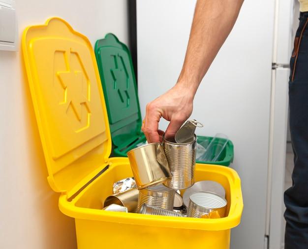 L'uomo lancia il barattolo di latta in uno dei tre contenitori per lo smistamento della spazzatura