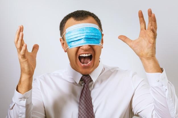 L'uomo in cravatta urla con una maschera medica sugli occhi depressione dovuta al coronavirus