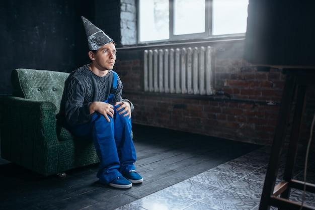 Uomo con cappuccio di carta stagnola guarda la tv, fobia della telepatia