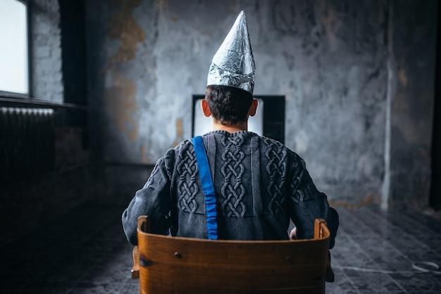 L'uomo con il casco di carta stagnola guarda la tv, vista posteriore. concetto di paranoia, ufo, teoria del complotto, protezione dal furto del cervello, fobia