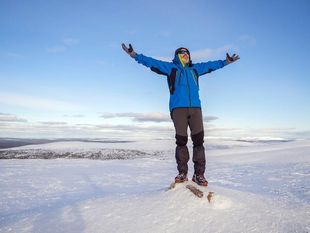 Un uomo in cima a una montagna innevata con le mani in alto
