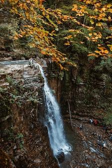 Uomo in cima alla cascata nello spazio della copia della foresta autunnale