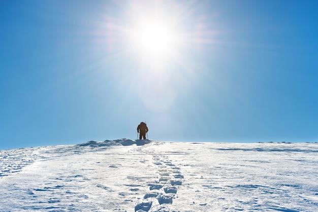 Un uomo sulla cima della montagna invernale con la neve