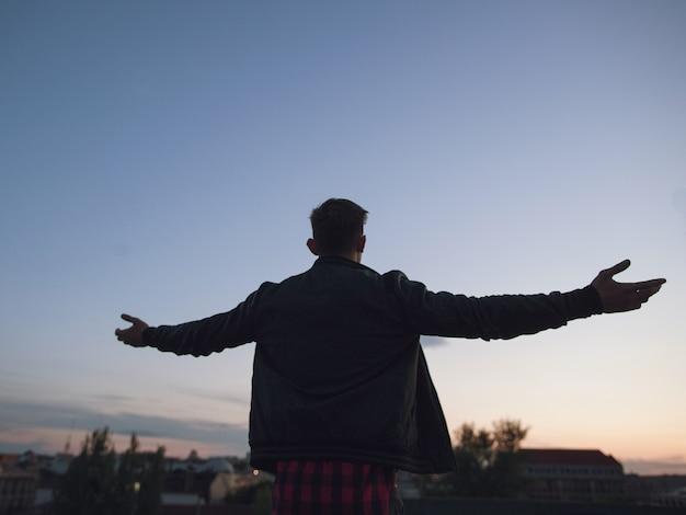 L'uomo in cima al mondo. ciao mondo. siluetta del giovane capo maschio sul fondo del cielo blu. nuovo business di successo, mattina solitaria, libertà e libertà nel concetto di vita