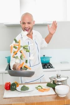 Uomo che tira le verdure in cucina