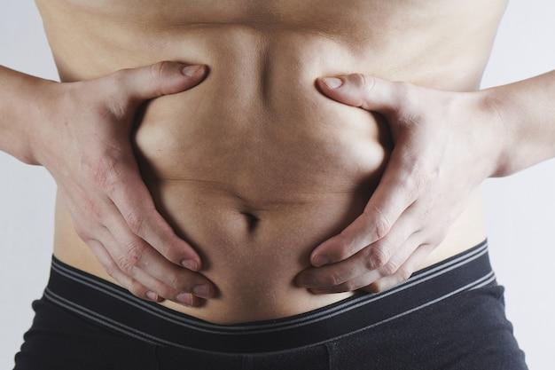 L'uomo tocca il suo primo piano grasso della pancia, obesità, perdita di peso maschile e concetto di dieta
