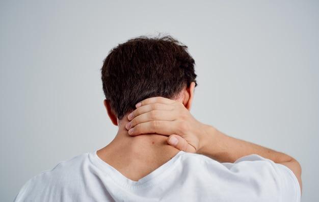 L'uomo si tocca il collo con la sua mano infortunio dolore problemi di osteocondrosi con la colonna vertebrale